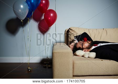 Waist-up portrait of bearded man with red clown nose sleeping on sofa after wild party, white bear lying under his head