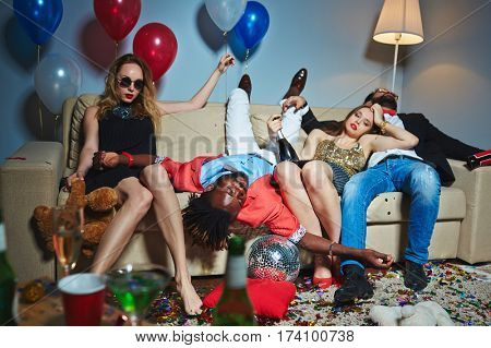 Two beautiful girls relaxing on sofa after New Year party while their drunken male friends having nap, all floor covered with confetti