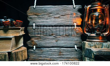 Rustic smoking pipes for on wood ashtray. Old books stack, retro-styled lamp and triple wooden signboard. Isolated over black