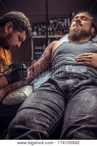 Professional tattooer makes tattoo in tatoo salon./Tattoo artist at work in tattoo parlor.