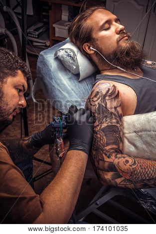Tattooer doing tattoo in tattoo studio./Man wearing gloves posing in tatoo salon.
