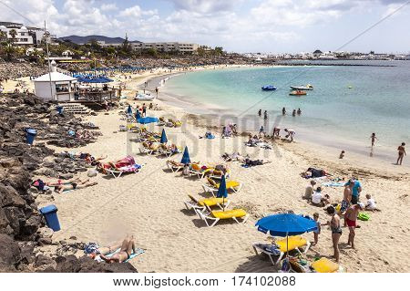 LANZAROTE SPAIN - APR 3 2012: Unidentified people enjoy a sunny day on the beach of Playa Dorada on Canary island in Lanzarote Spain