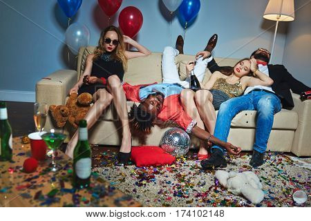 Messy room after wild house party, three tipsy stylish friends relaxing on couch while blond-haired woman with teddy bear posing for photography