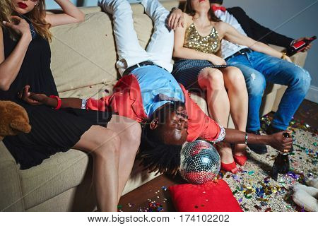 Portrait of middle-aged Afro-American man lying upside-down on couch while his friends sitting next to him with closed eyes after night party