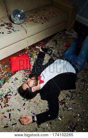 Intoxicated bearded man with bow tie having nap on carpet covered with confetti after wild house party