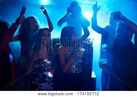 Young pretty girls in glam clothes hanging out with their male friends in night club, dancing with cocktails and enjoying night