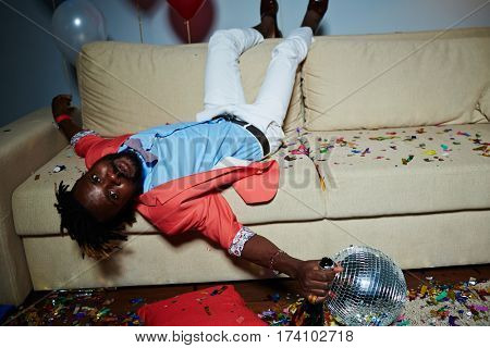 Tipsy African American man with short dreadlocks lying upside-down on brown sofa and looking at camera after New Year party