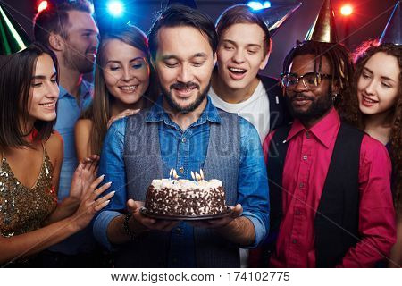 Young bearded man standing among close friends, holding birthday cake with candles and making a wish