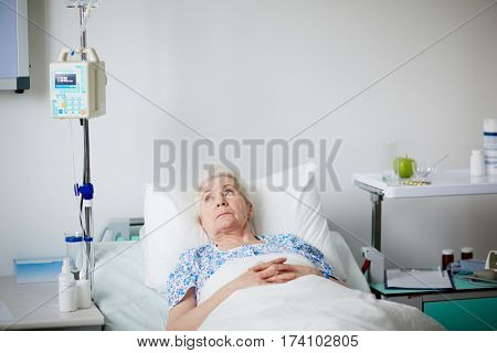 Sick elderly woman resting in hospital bed after getting drop bottle treatment, looking melancholy at ceiling, thinking about her long life