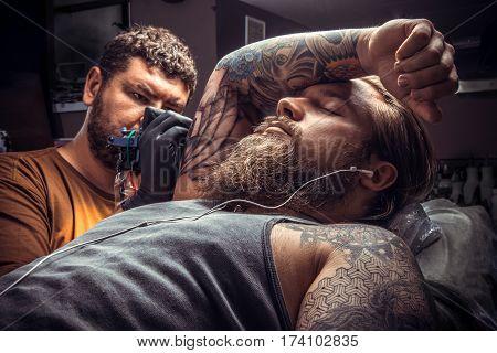 Professional tattooist makes tattoo in tattoo studio./Tattoo master working tattooing in tattoo parlor. poster