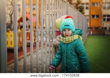 Two girls want to enter the closed playground in autumn
