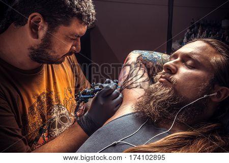 Tattoo master working tattooing in studio./Tattoo specialist create tattoo in tatoo salon.