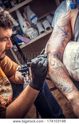 Tattoo artist works in studio./Man wearing gloves create tattoo in tattoo studio.