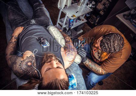 Tattoo master makes tattoo pictures in tattoo studio./Master makes cool tattoo in salon.
