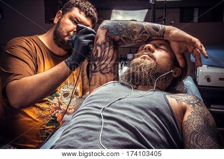 Professional tattooer working tattooing in tattoo studio.