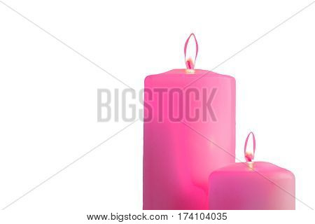 Two pink burning candles isolated on white background