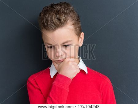 Casual thinking guy - caucasian male model. Close-up emotional portrait of teen boy. Thoughtful teenager in front of a big blackboard. Handsome smart serious ponder child.