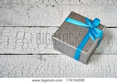Gift birthday Christmas present concept - silver gift box with blue ribbon on white painted wooden background. Top view