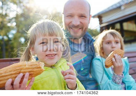 Blond-haired little girls sitting on wooden park bench with their bald dad and eating tasty hotdogs, waist-up portrait