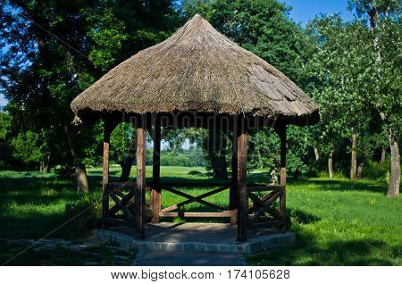 Retro looking wooden gazebo with a straw roof near golf course at Ada, Belgrade, Serbia