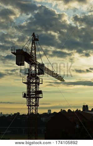 Yellow construction crane silhouette against cloudy sky at sunrise in Belgrade, Serbia