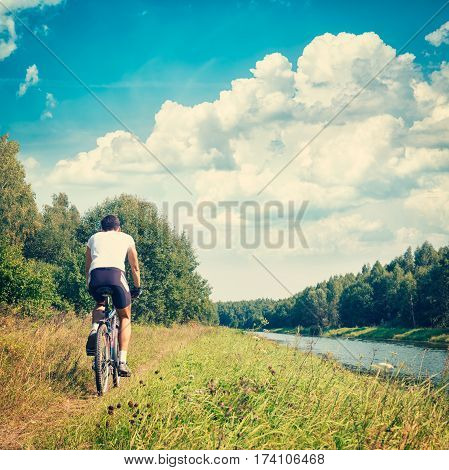Rear View of a Man Riding a Bike on River Bank. Beautiful Nature Background. Healthy Lifestyle and Leisure Activity Concept. Toned and Filtered Instagram Styled Photo with Copy Space.