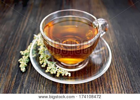 Tea With Gray Wormwood In Glass Cup On Board