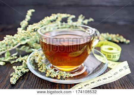 Tea With Wormwood In Glass Cup And Meter On Dark Board