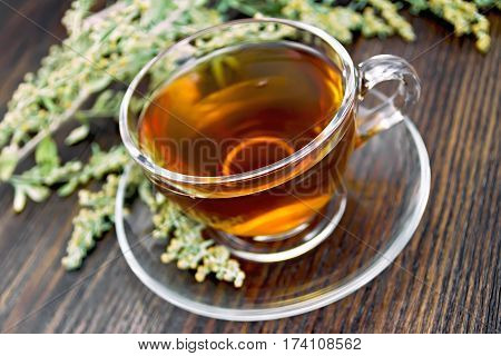 Tea With Wormwood In Glass Cup On Dark Board