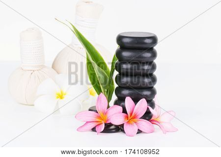 Spa concept with hot stones, herbal compress balls and flowers on white background