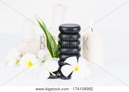 Spa with hot stones, herbal compress balls, candle and flowers on white background