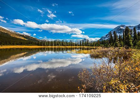 Sky and clouds reflected in the smooth water in the lake. Rocky Mountains on a sunny autumn day. The concept of ecotourism