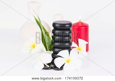 Traditional spa with herbal compress ball, hot stones and flowers on white background