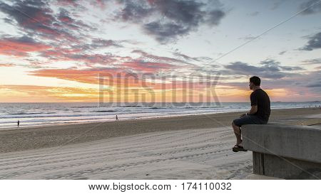 Person sat watching sunrise on Gold Coast Surfers Paradise beach