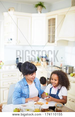 Lovely family having good time together in kitchen: little girl with long curly hair playing with heads of silicone brushes while attractive young mother looking at  her