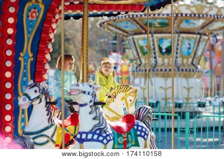 Two blond-haired little girls in bright windbreakers sitting on carousel horses and smiling happily
