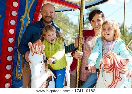Pretty little girl in green windbreaker and her elder sister riding on carousel while their cheerful parents standing behind them and posing for photography