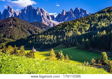 Warm autumn in the Dolomites, Tirol.  The church of Santa Maddalena. Rocky peaks and forested mountains surrounded by green Alpine meadows.  The concept of ecological and active tourism
