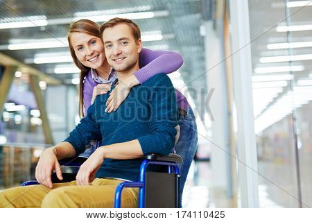 Portrait of young happy couple: pretty girl hugging her smiling handicapped boyfriend in wheelchair