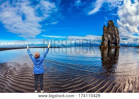 The Basalt rock - Monster Hvitsercur during an ocean outflow. Woman in blue jacket admires natural wonder. Concept of extreme northern tourism in Iceland