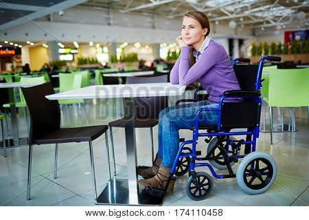 Young physically impaired girl sitting in wheelchair at mall food court and waiting for her friend with pensive face expression