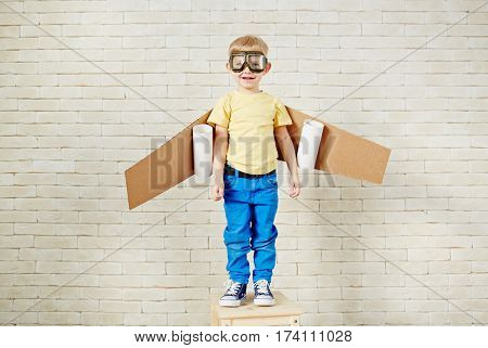 Funny little boy in aviator goggles and with carton airplane wings behind his back standing on wooden chair and looking at camera with smile
