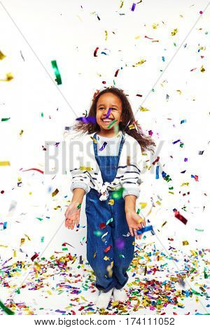 Studio portrait of little African girl jumping and tossing bright confetti in the air laughing joyfully