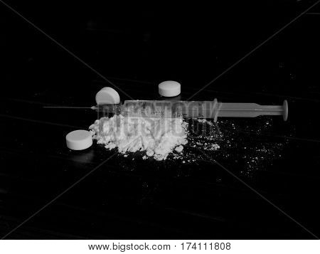 Injection syringe on cocaine drug powder pile and pills on black background