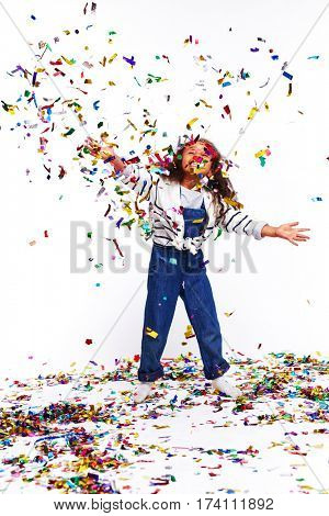 Studio portrait of little African girl dressed in blue jeans overalls playing with confetti, tossing it high up and laughing