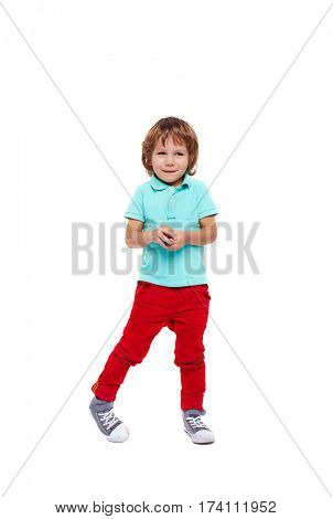 Full body portrait of shy little boy dressed in bright colorful clothes standing giggling and  posing awkwardly against white background