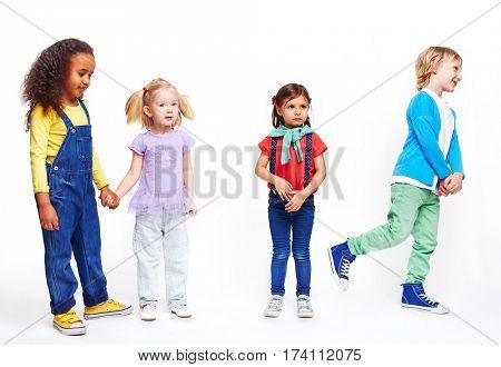 Studio portrait of children against white background: cutout of four kids in bright clothes, two girls holding hands, boy running and confused little girl