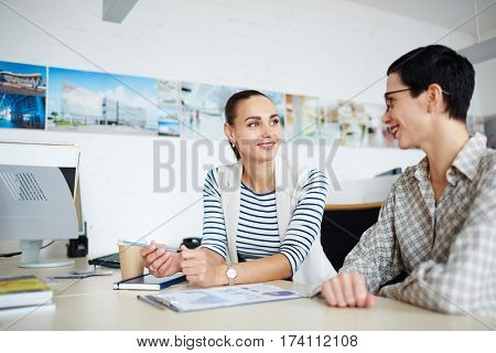 Portrait of two businesswomen, one mature and one young, sitting at desk together in modern office, discussing something and smiling during meeting