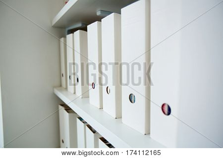 Row of white identical documentation folders on shelf of file cabinet in office