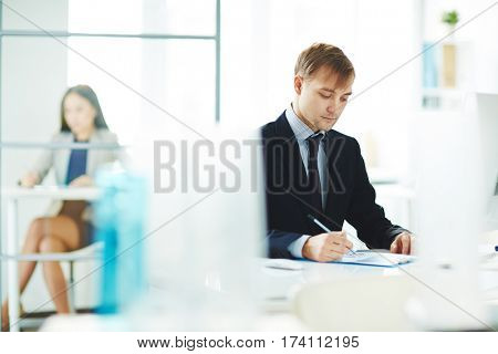 Portrait of young business analyst checking statistics report with graphs while sitting at workplace in modern light office